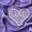 Pearl necklace in heart shape on blue silk fabric — Stock Photo