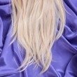 Blonde straight hair on blue silk fabric, hair care — Stock Photo