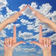 House made of female hands over blue sky with clouds. concept symbol home — Stock Photo #29077561