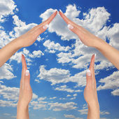 House made of female hands over blue sky with clouds. concept symbol home — Stock Photo