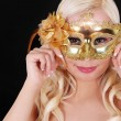 jeune fille blonde avec un masque Carnaval or sur fond noir. mascarade. Halloween — Photo #29093323
