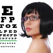 Optician. Beautiful brunette wearing glasses and Snellen eye exam chart isolated on white background — Stok fotoğraf