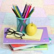 Back to school concept. An apple, colored pencils and glasses on pile of books over map — Stock Photo #29850017