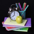 Back to school concept. An apple, colored pencils and alarm clock on pile of books over black background — Stock Photo