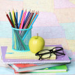 Back to school concept. An apple, colored pencils and glasses on pile of books over map — Stock Photo #29888959