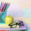 Back to school concept. An apple, colored pencils and glasses on pile of books over map — Stock Photo #29889295