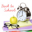 Back to school concept. An apple, alarm clock and glasses on pile of books isolated on white background — Foto de Stock