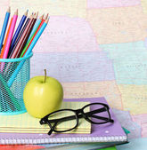 Back to school concept. An apple, colored pencils and glasses on pile of books over map — Stock Photo
