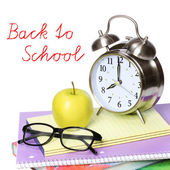 Back to school concept. An apple, alarm clock and glasses on pile of books isolated on white background — Stock Photo