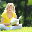 Girl reading the book. Blonde beautiful young woman with book sitting on the grass. Outdoor. Sunny day. Looking at the camera — Stock Photo