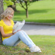 Girl reading the book. Blonde beautiful young woman with book sitting on the grass and leaning to the tree. Outdoor. — Stock Photo
