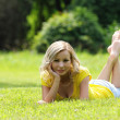 Blonde girl laying on the grass and smiling. Looking at the camera. Outdoor. Sunny day. Rest and Picnic — Stock Photo #30064725
