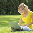 Girl with laptop. Blonde beautiful young woman with notebook sitting on the grass. Outdoor. Sunny day. Back to school — Stock fotografie