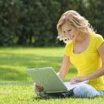 meisje met laptop. blonde mooie jonge vrouw met laptop zittend op het gras. buiten. zonnige dag. terug naar school — Stockfoto