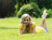 Blonde girl laying on the grass and smiling. Looking at the camera. Outdoor. Sunny day. Rest and Picnic — Stockfoto