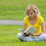 meisje lezen van het boek. blonde mooie jonge vrouw met boek zittend op het gras. buiten. zonnige dag. terug naar school — Stockfoto