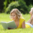 Girl reading the book. Blonde beautiful young woman with book lying on the grass. Outdoor. Sunny day. Back to school — Foto de Stock
