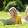 Girl reading the book. Blonde beautiful young woman with book lying on the grass. Outdoor. Sunny day. Back to school — 图库照片