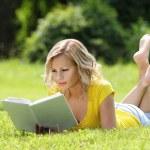 meisje lezen van het boek. blonde mooie jonge vrouw met boek liggen op het gras. buiten. zonnige dag. terug naar school — Stockfoto
