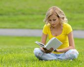 Girl reading the book. Blonde beautiful young woman with book sitting on the grass. Outdoor. Sunny day. Back to school — Stock Photo