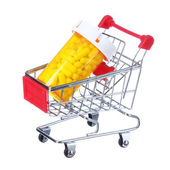 Pill bottle in shopping cart isolated on white. concept — Stock Photo