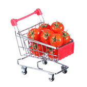 Tomatoes in shopping cart isolated on white. concept. — Stock Photo