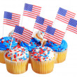 Patriotic cupcakes decorated with American Flags and blue, white cream with red stars sprinkles on the top, isolated on white background. — Stock Photo