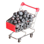 Ripe blueberries in shopping cart isolated on white. concept. — Stock Photo