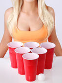 Beer pong. Red plastic cups with ping pong ball and blonde girl in sexy tank top. — Stock Photo