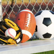 Sports balls. Soccer ball, american football and baseball in yellow glove. Outdoors — Stock Photo #30885407