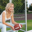 Happy blonde girl with american football. Smiling cheerful beautiful young woman sitting on the bench. Outdoors. Fan of football team is watching the game — Stockfoto