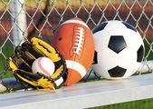 спортивные мячи. мяч футбол, американский футбол и бейсбол в желтой перчатке. на открытом воздухе — Стоковое фото