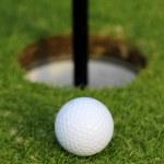 Yeşil çimenlerin üzerinde fincan içine düşmek için golf topu. portre — Stok fotoğraf