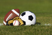 Sports balls on the field with yard line. Soccer ball, American football and Baseball in yellow glove on green grass. Outdoors — Stock Photo
