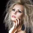 Стоковое фото: Fashion blonde girl. Beautiful blonde woman with professional makeup and hairstyle, over black background. Vogue style model