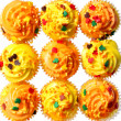 Cupcakes with yellow and orange frosting and colored sprinkles. Background. Sweet food for Halloween — Stock Photo