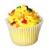Cupcake with yellow frosting and colored sprinkles isolated on white. Sweet food — Stock Photo