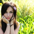Brunette girl on green grass at summer park. Portrait of young beautiful woman — Stock Photo