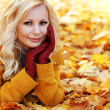 Foto de Stock  : Blonde girl in Autumn Park with Maple leaves. Fashion Beautiful