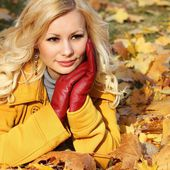 Blonde girl in Autumn Park with Maple leaves. Fashion Beautiful — Stock Photo