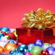 Christmas Gift with Gold Bow and Colorful Balls over red backgro — Foto Stock