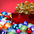 Christmas Gift with Gold Bow and Colorful Balls over red backgro — Stok fotoğraf