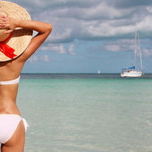 Sexy girl on tropical beach. Beautiful young woman with sun hat — Stock Photo