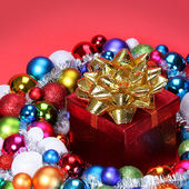 Christmas Gift with Gold Bow and Colorful Balls over red backgro — Stock fotografie