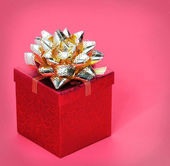 Christmas Gift Box with Gold Ribbon Bow, over red background — Stock Photo