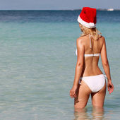 Santa Girl on Tropical Beach. Beautiful blonde young woman in re — Stock Photo