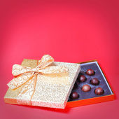 Gold Candy Box with Truffles over red background. Christmas Gift — Foto de Stock