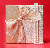 Gift Box with Pearl Necklace over red background. Christmas Pres — Foto Stock