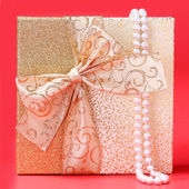 Gift Box with Pearl Necklace over red background. Christmas Pres — Stock fotografie