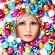 Christmas Woman with Colored Balls. Face of Beautiful Girl with Fashion Makeup and Shiny Christmas Baubles. — Foto de Stock